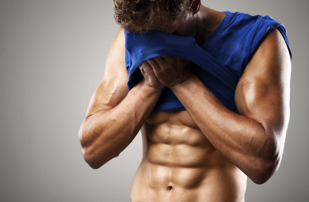 muscular man wiping of sweat with his t-shirt
