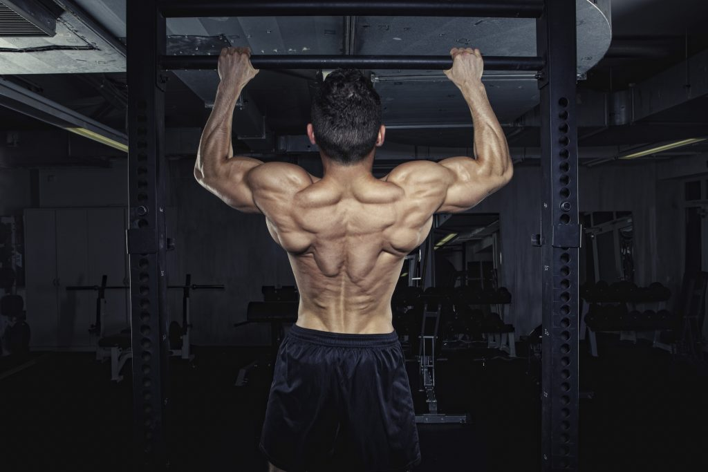 Physical athlete doing chin-ups
